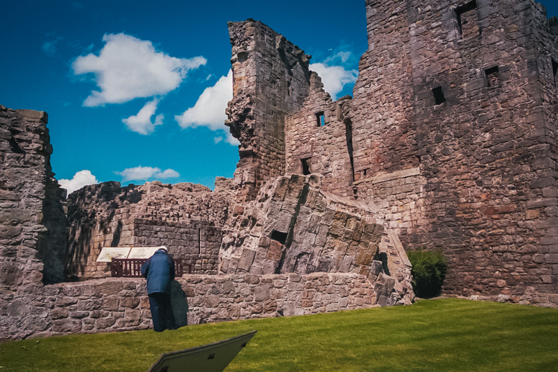 the oldest part of aberdour, with a fallen tower and a gentleman fixing the wall