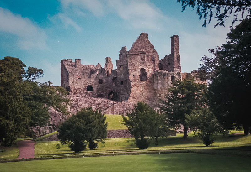 The yellow stone bulk of DIrleton sits on a stone bluff overlooking gardens